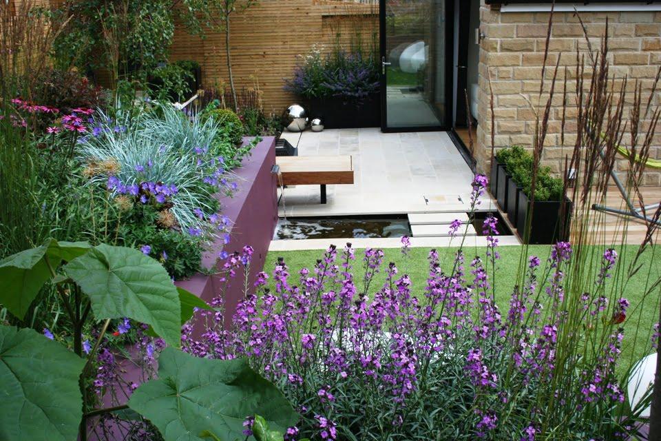 Alyvinės spalvos atraminė sienutė gražiai suskamba kartu su augalais. Nuotrauka iš www.inspiredgardendesign.co.uk