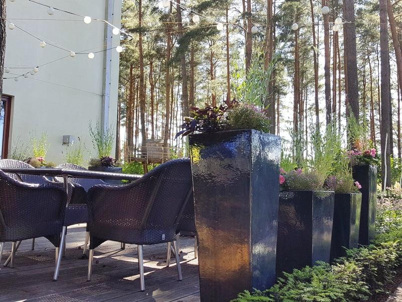 Aukšti vazonai, kuriuose gėlių kompozicijos gali būti keičiamos kelis kartus per metus. Pavyzdžiui, Ansis augalų derinius keičia tris kartus per metus. Šį vasaros sezoną vazonuose dominuoja ryškiaspalvės žydinčios gėlės. Šis vertikalus elementas skiria valgomojo zoną nuo likusios sodo dalies.