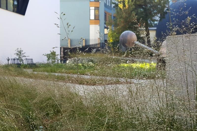 """Subtilūs daugiamečiai varpiniai augalai pabrėžia stambių ir sunkių skulptūrų svarbą sode. Dešinėje - Vlado Urbanavičiaus skulptūros """"Kuoka"""" fragmentas. Nuotr. L.Liubertaitė"""