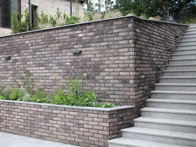 šlaito apželdinimas. Aukšta siena ir laiptai tapo savotišku fortu, laikančiu aukštą šlaitą. Jų masyvumui sušvelninti buvo įrengtos žaliuojančių augalų klombos. Augalų žaluma ir laisvos formos sukuria kontrastą betoninės sienos pilkumui ir griežtumui. Nuotr. L. Liubertaitė