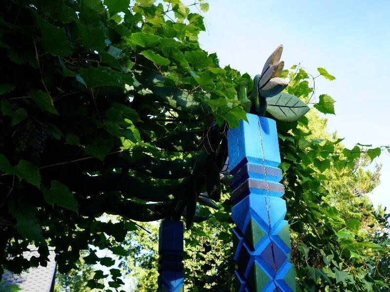 Ryškių spalvų pergolė savo puošnumu prilygsta tikriems kiemo vartams. Nuotr. Lina Liubertaitė